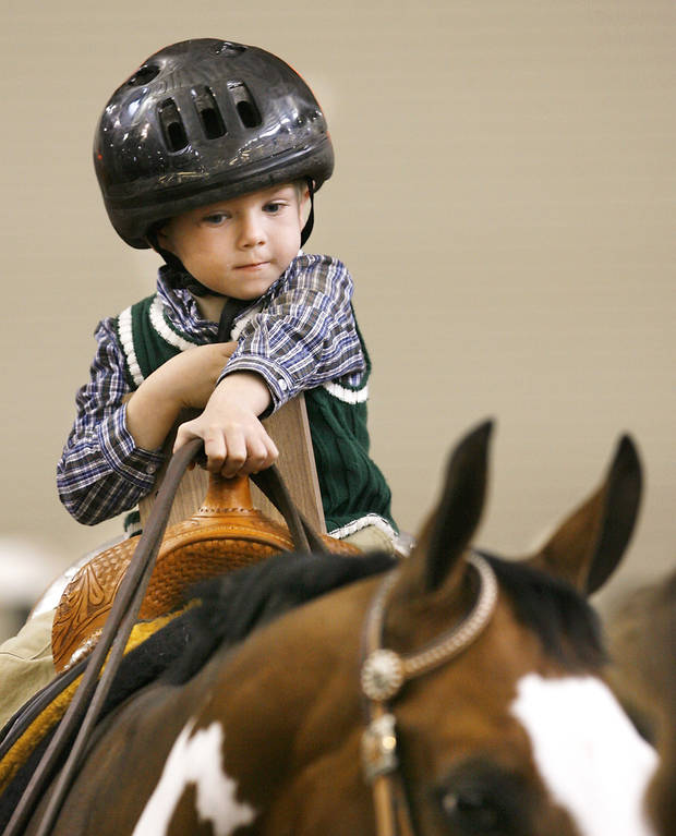 photo - Jimmy, 4, of Shawnee rides Patch the horse at State Fair Park during a special exhibition at the Oklahoma Holiday Classic, a horse show organized by the Oklahoma Paint Horse Club. Jimmy and his two brothers were among nine riders who participated in horse therapy exhibition. Photo BY JIM BECKEL, THE OKLAHOMAN