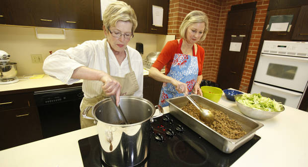 Sally Bentley, left, and Mary Lynn West prepare taco salads for delivery by Meals on Wheels volunteers at Westminster Presbyterian Church in Oklahoma City, Oklahoma , Monday, May 24, 2011. Photo by Steve Gooch ORG XMIT: KOD