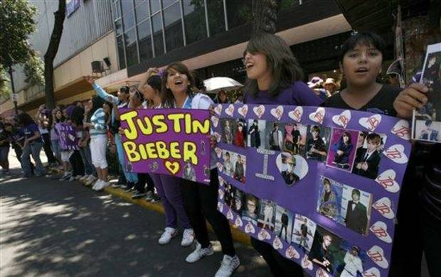 photo - Fans hold images of pop starJustin Bieber in Mexico City's main historic plaza, the Zocalo, Sunday, June 10, 2012. The Beliebers have arrived in the chaotic streets of Mexico City, adolescents in purple and white and braving two nights on roach-infested sidewalks for a chance to be closest to the stage when teenage superstar Justin Bieber puts on a free concert Monday evening on the capital's vast central plaza. (AP Photo/Marco Ugarte)