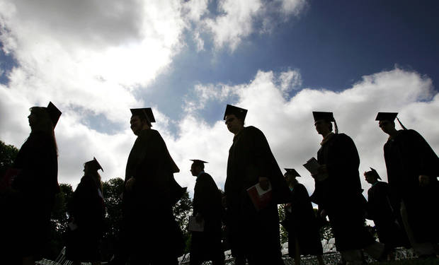 University students in their caps and gowns are silhouetted as they line up for graduation ceremonies in 2016. [AP Photo]