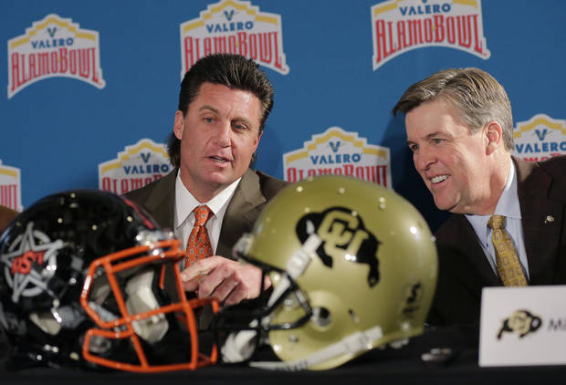 Oklahoma State head coach Mike Gundy, left, and Colorado head coach Mike MacIntyre, right, compare helmets before a news conference, Thursday, Dec. 8, 2016, in San Antonio. Oklahoma State and Colorado will play in the Alamo Bowl on Dec. 29. (AP Photo/Eric Gay)