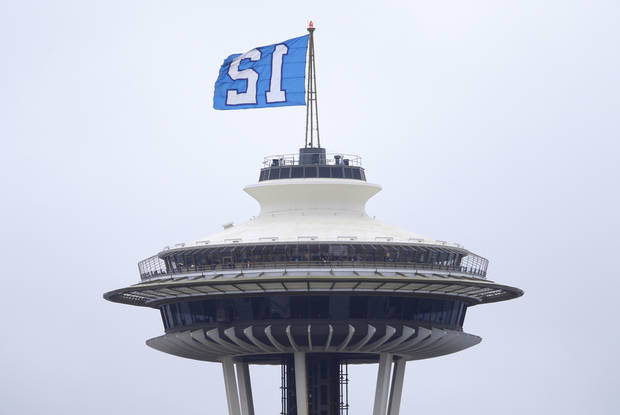 photo - The Seahawks' 12th Man flag flies from the top of the Space Needle as viewed from Kerry Park, Friday, Jan. 10, 2014, in Seattle.  (AP Photo/Ted S. Warren)