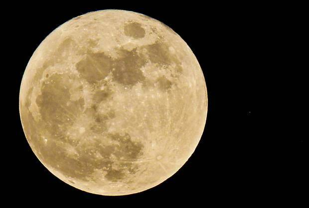 The full moon is a tint of orange as it hangs in the sky over Oklahoma on May 27, 2010, in Oklahoma City. Photo by Chris Landsberger, The Oklahoman