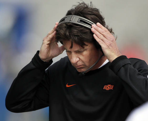Oklahoma State head coach Mike Gundy adjusts his headset during the first half of Saturday's game vs. Kansas in Lawrenec, Kan. [AP PHOTO]