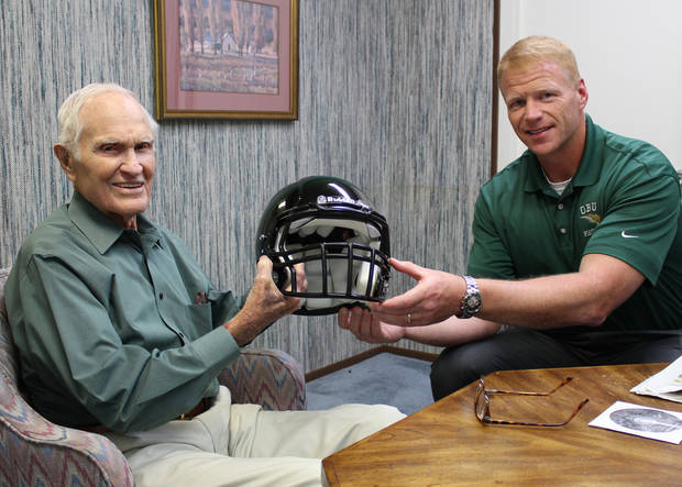 photo - Former OBU football player Larry Harris, left, holds a helmet with new OBU coach Chris Jensen. Photo provided.