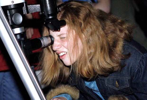 photo - Sarah Lenkem, 13, of Norman, looks through a telescope during an April stargazing session outside of Sam Noble Oklahoma Museum of Natural History in Norman. OKLAHOMAN ARCHIVE PHOTO