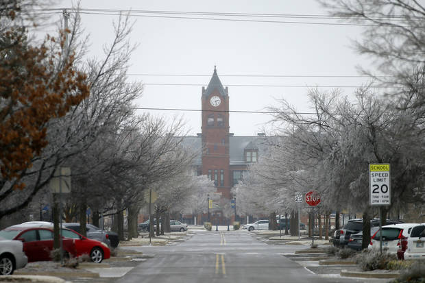 A layer of ice covers the street and trees west of Old North at the University of Central Oklahoma in Edmond on Wednesday. [Bryan Terry/The Oklahoman]