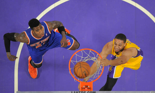 photo - Los Angeles Lakers forward Xavier Henry, right, dunks as New York Knicks guard Iman Shumpert defends during the first half of an NBA basketball game, Tuesday, March 25, 2014, in Los Angeles. (AP Photo/Mark J. Terrill)