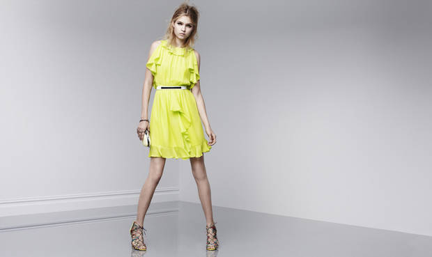 "photo - One trick to ""dressing rich"" is to wear a ""statement"" dress, according to fashion expert Anna Johnson. Here is a bright lemon yellow ruffled dress with statement shoes from Prabal Gurung's new designer collection at Target, coming out Feb. 10."