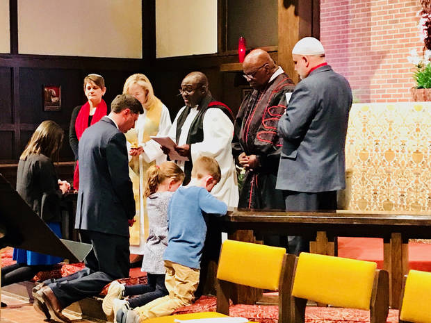 "Rachel Holt, her husband Oklahoma City Mayor-elect David Holt, and their two children kneel at the altar as Oklahoma City spiritual leaders pray for them on Sunday at ""A Prayer for our City"" at St. Augustine of Canterbury Episcopal Church. The religious leaders, from left, are Rabbi Vered Harris, the Rev. Dawn Enderwood, the Rev. Joseph Alsay, the Rev. Major Jemison and Imam Imad Enchassi. [Photo by Carla Hinton, The Oklahoman]"