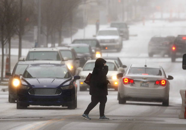 A pedestrian walks in front of traffic on a downtown street. Oklahoma City residents faced a second day of sub-freezing temperatures, blustery winds and a mix of sleet and ice that quickly covered road surfaces and sidewalks Wednesday afternoon, Feb. 21, 2018. Photo by Jim Beckel, The Oklahoman