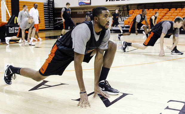 photo - Oklahoma State forward Michael Cobbins stretches before practice following an NCAA college basketball media day in Stillwater, Okla., Monday, Oct. 22, 2012. (AP Photo/Sue Ogrocki) ORG XMIT: OKSO108