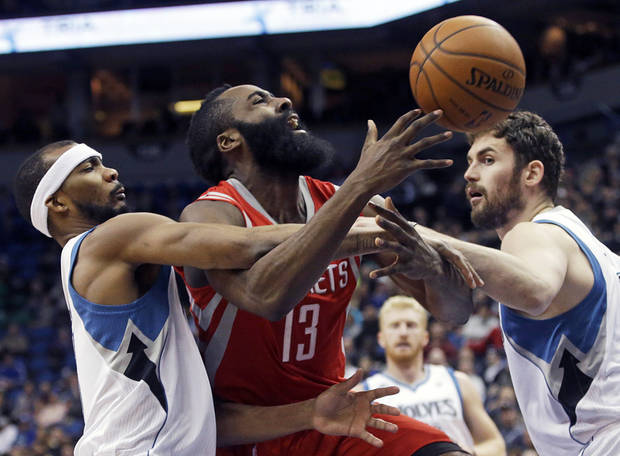 photo - Houston Rockets' James Harden, center, is fouled by Minnesota Timberwolves' Corey Brewer, left, as Kevin Love also thwarts a scoring attempt in the second half of an NBA basketball game, Monday, Feb. 10, 2014, in Minneapolis. Harden scored 19 points. The Rockets won 107-89. (AP Photo/Jim Mone)