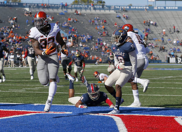 Oklahoma State's Chris Carson (32) scores in front of Kansas's Bryce Torneden (12) and Marnez Ogletree (10) in the fourth quarter during the college football game between the Oklahoma State Cowboys (OSU) and the Kansas Jayhawks at Memorial Stadium in Lawrence, Kan., Saturday, Oct. 22, 2016.   Photo by Sarah Phipps, The Oklahoman