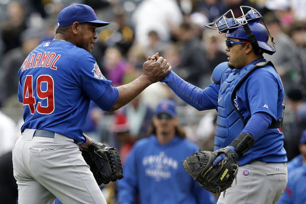 photo - Chicago Cubs relief pitcher Carlos Marmol, left, celebrates with catcher Dioner Navarro after getting the final out in the ninth inning to preserve a 3-2 win over the Pittsburgh Pirates in a baseball game in Pittsburgh, Thursday, April 4, 2013. (AP Photo/Gene J. Puskar) ORG XMIT: PAGP113