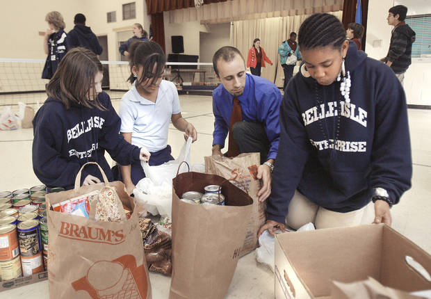 photo - Belle Isle Enterprise Middle School students Bethany Goodman, 11, Mikayla Nevills, 12, science teacher Dan Covey and Kori Long, 11, sort food donations to assist families in need this Thanksgiving.