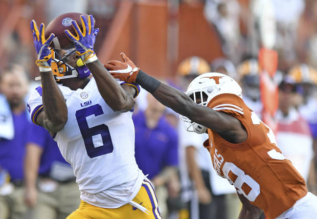 LSU's Terrace Marshall Jr. hauls in a pass with Texas' Kobe Boyce defending. (Photo by Hilary Scheinuk/The Advocate)