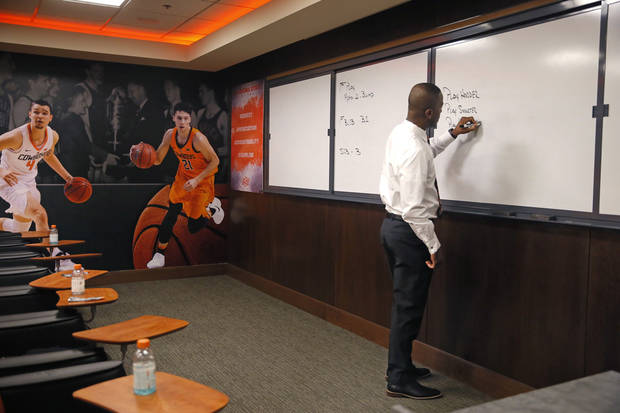 Mike Boynton writes on a board in a team meeting room Wednesday. [Bryan Terry/The Oklahoman]