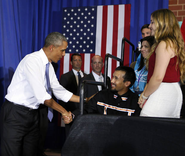 President Barack Obama shakes hands with a member of the audience on July 15, 2015 as he walks on stage before speaking at Durant High School. [Photo by Nate Billings, The Oklahoman]
