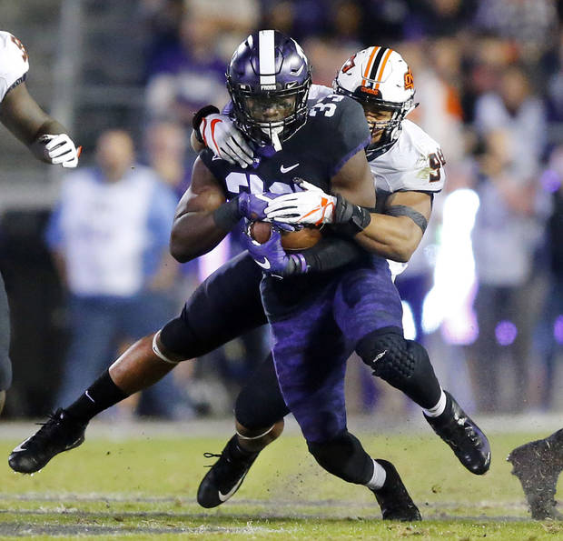 Oklahoma State defensive end Jordan Brailford (94) makes a diving tackle of TCU running back Sewo Olonilua (33) during the second quarter of an NCAA college football game in Fort Worth, Texas, Saturday, Nov. 24, 2018. (Tom Fox/The Dallas Morning News via AP)