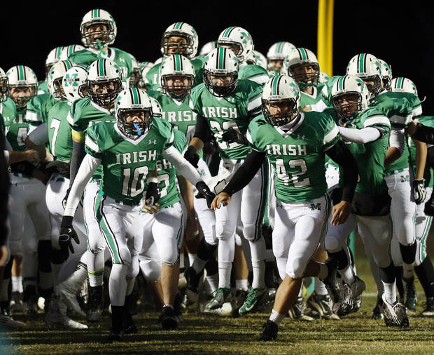 photo - The Bishop McGuinness Fighting Irish take the field before a high school football game between Bishop McGuinness and Guthrie at Bishop McGuinness Catholic High School in Oklahoma City, Friday, Oct. 26, 2012. Photo by Nate Billings, The Oklahoman