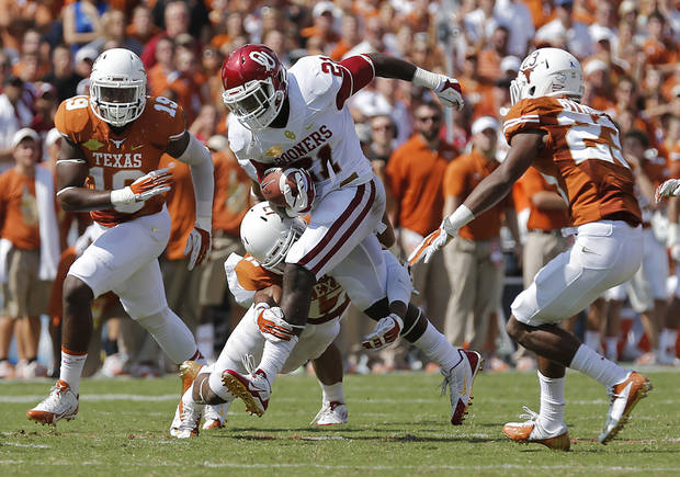 OU's Keith Ford (21) runs through the Texas defense during the Red River Rivalry college football game between the University of Oklahoma Sooners (OU) and the University of Texas Longhorns (UT) at the Cotton Bowl Stadium in Dallas, Saturday, Oct. 12, 2013. Photo by Chris Landsberger