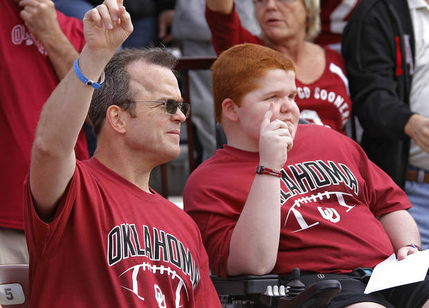 photo - KEEGAN ERBST: Scott Erbst and his son Keegan watch the action on the field during the college football game between the University of Oklahoma Sooners (OU) and Baylor University Bears (BU) at Gaylord Family - Oklahoma Memorial Stadium on Saturday, Nov. 10, 2012, in Norman, Okla.  Photo by Chris Landsberger, The Oklahoman