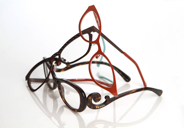 photo - Eyelgasses have gone from nerd necessity to fashion accessory. Shown, from left are pairs from Fiction, l.a. Eyeworks,  and Prada. (Kirk McKoy/Los Angeles Times/MCT)