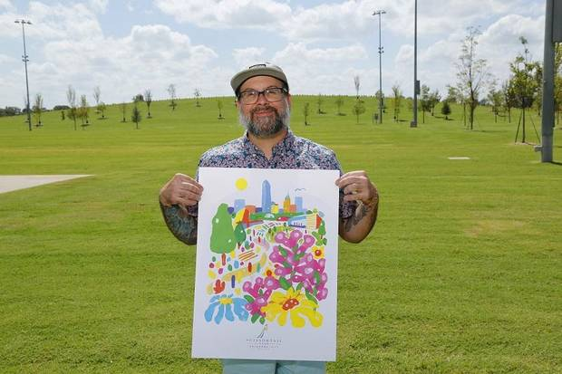 Kris Kanaly holds a copy of the limited-edition poster he designed to mark the grand opening of Scissortail Park. [Photo by Doug Hoke]