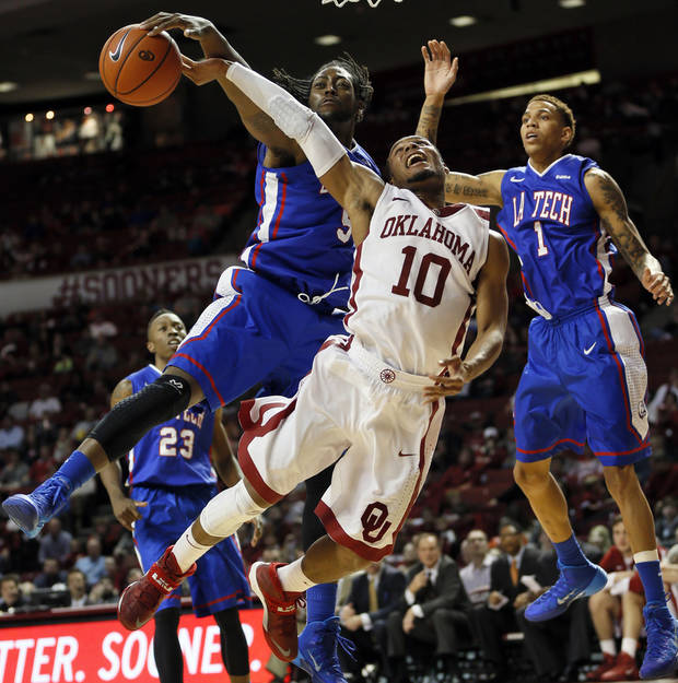 photo - Louisiana Tech's Chris Anderson, left, fouls OU's Jordan Woodard, center, during Monday night's game. Louisiana Tech won 102-98 in overtime.  Photo by Nate Billings, The Oklahoman