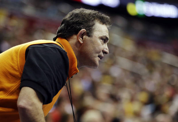 photo - Oklahoma State coach John Smith watches a match between Alex Dieringer and Ohio's Spartak Chino in a 157-pound match at the NCAA Division I college wrestling championships, Thursday, March 21, 2013, in Des Moines, Iowa. (AP Photo/Charlie Neibergall)