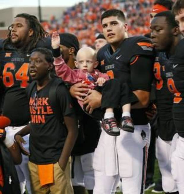 Oklahoma State quarterback Mason Rudolph holds Gavin following the Cowboys' 36-34 victory over Kansas State. Gavin attended the game with the Special Spectators, a nationwide program that provides game-day experiences for kids battling serious illness. [Photo by Nate Billings, The Oklahoman]