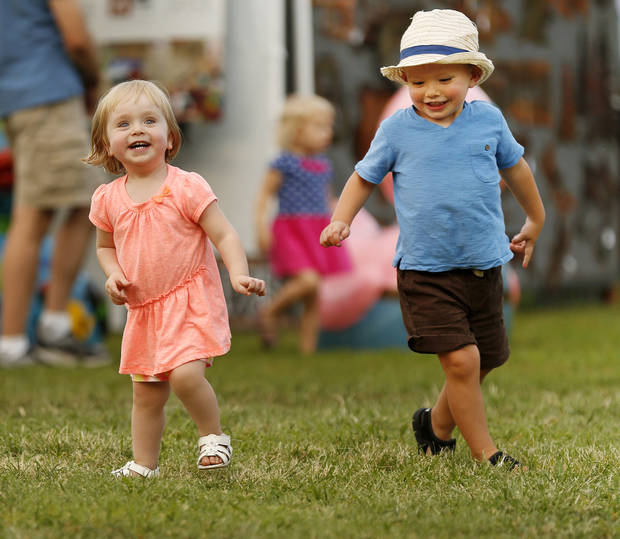 photo -  Two-year-old cousins Annabelle Harper and Roman Harper play during Midsummer Nights' Fair at Lions Park in Norman. PHOTO BY NATE BILLINGS, THE OKLAHOMAN   NATE BILLINGS -