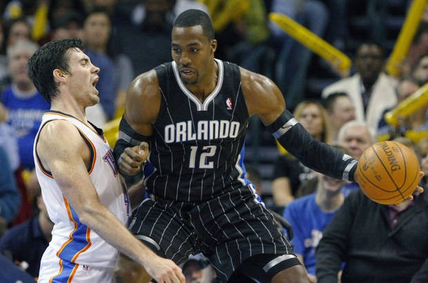 photo - Orlando Magic's Dwight Howard (12) drives to the basket against Oklahoma City Thunder's Nick Collison, left, during the third quarter of an NBA basketball game in Oklahoma City, Sunday, Dec. 25, 2011. The Thunder won 97-89. (AP Photo/Alonzo Adams) ORG XMIT: OKAA110