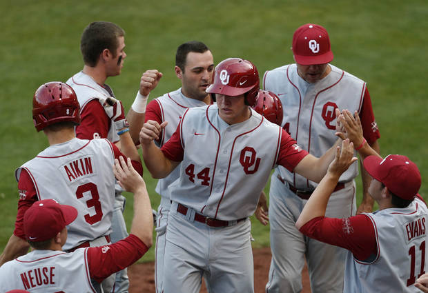 photo - Oklahoma's Austin O'Brien, center front, and Anthony Hermelyn, center rear, are greeted at the dugout after scoring against Oklahoma State during an NCAA college baseball game in Tulsa, Okla., on Saturday, May 17, 2014. (AP Photo/Tulsa World, Matt Barnard)