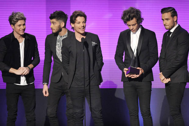 "photo - From left, Niall Horan, Zayn Malik, Louis Tomlinson, Harry Styles, and Liam Payne of musical group One Direction, accept the award for favorite album - pop/rock for ""Take Me Home"" at the American Music Awards at the Nokia Theatre L.A. Live on Sunday, Nov. 24, 2013, in Los Angeles. (Photo by John Shearer/Invision/AP)"