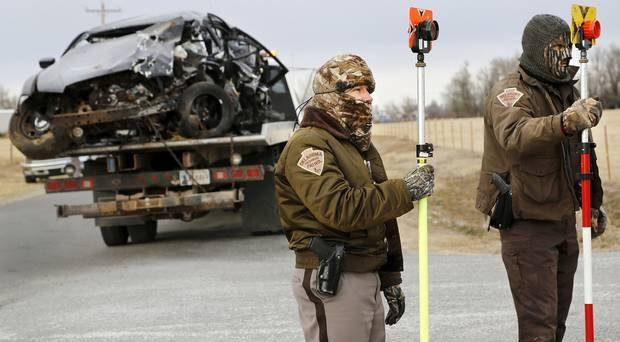 photo - The vehicle driven by a Burns Flat police officer is removed from the crash site as two OHP investigators gather information. Photo by Jim Beckel, The Oklahoman