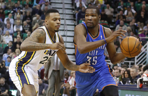 photo - OKC's Kevin Durant, right, is defended by Utah's Brandon Rush during first half action in Salt Lake City on Tuesday. Durant scored 48 points in a 112-101 loss. AP Photo