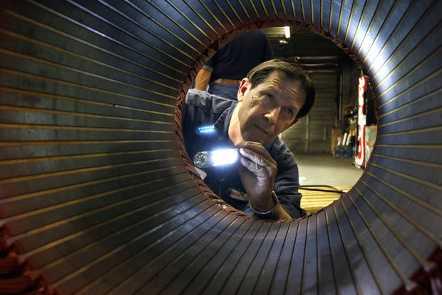 photo -  Motor technician Thomas Shotts inspects the inside of an industrial motor at Capitol Electric Motor Repair in southwest Oklahoma City. The company is celebrating 50 years in business. Photos by Paul Hellstern, The Oklahoman   PAUL HELLSTERN -  Oklahoman