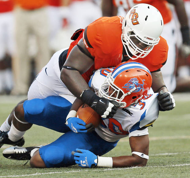 OSU's Calvin Barnett (99) brings down Lereginald Veals (30) of Savannah State during the Cowboys' 84-0 rout in 2012. Games like OSU-Savannah State would be prohibited in the Big Ten, starting in 2016. (Photo by Nate Billings)