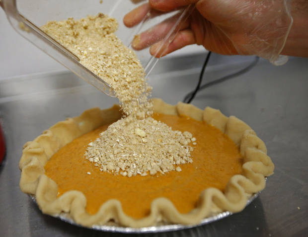 In this 2015 file photo, a crumble crust is poured on pumpkin pies at Pie Junkie in Oklahoma City. (Photo by Bryan Terry, The Oklahoman)