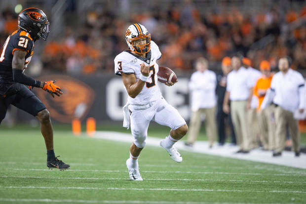 OSU quarterback Spencer Sanders runs against Oregon State. (Photo by Bruce Waterfield).