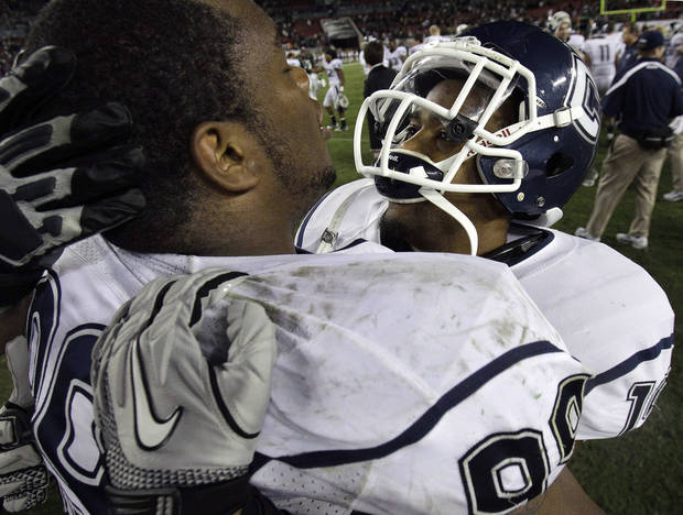 photo - Connecticut defensive tackle Kendall Reyes (99) celebrates with Kijuan Dabney (19) after the team defeated South Florida 19-16 to win the Big East conference title during an NCAA college football game Saturday, Dec. 4, 2010, in Tampa, Fla. AP Photo/Chris O'Meara
