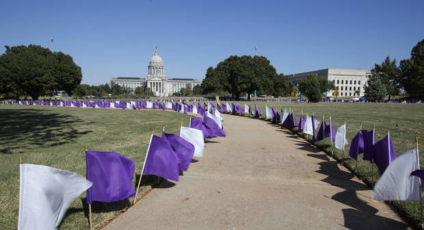 In this October 2015 file photo, purple and white flags are displayed outside the state Capitol in Oklahoma City as part of domestic violence awareness month. [Photo By Steve Gooch, The Oklahoman]