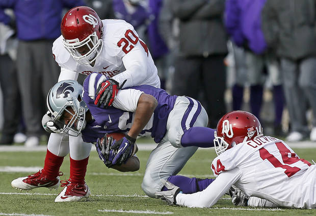 Oklahoma's Frank Shannon (20) and Aaron Colvin (14) bring down Kansas State's Tyler Lockett (16) during an NCAA college football game between the Oklahoma Sooners and the Kansas State University Wildcats at Bill Snyder Family Stadium in Manhattan, Kan., Saturday, Nov. 23, 2013