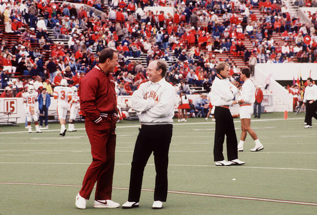 photo - University of Oklahoma (OU) college football coach Barry Switzer and Oklahoma State University (OSU) football coach Pat Jones visit on the field before the 11/7/87 Sooner-Cowboy contest in Norman.  The Sooners prevailed, 29-10. Staff photo by Doug Hoke taken 11/7/87; photo ran in the 11/5/88 Daily Oklahoman.