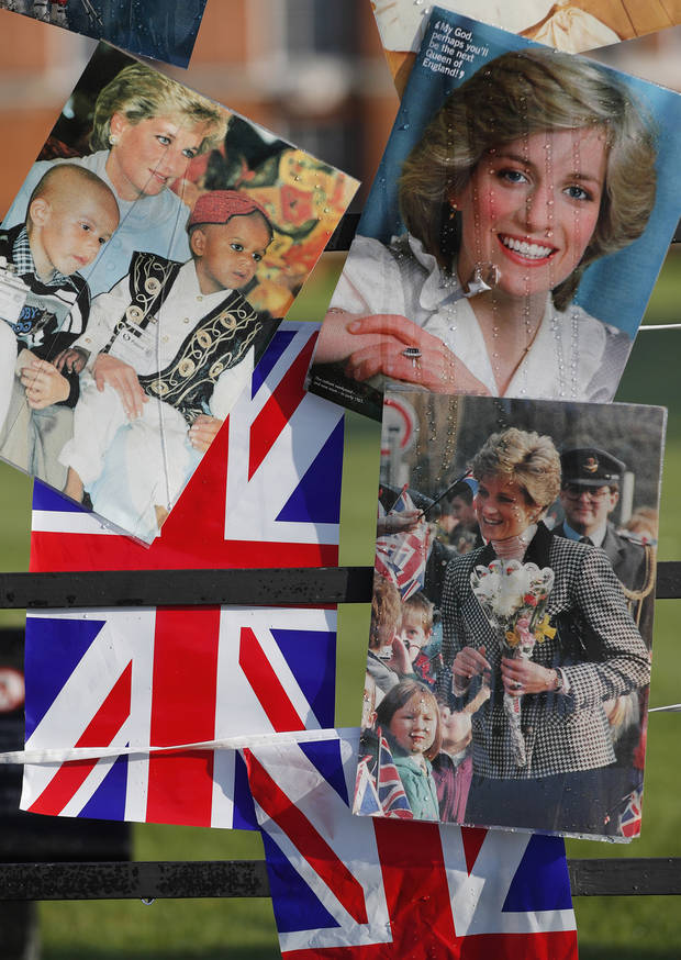 Pictures of the late Diana, Princess of Wales, hang on the fence outside Kensington Palace to pay tribute to her in London, Thursday, Aug. 31, 2017. The tributes are to mark the 20th anniversary of her death, in a car crash in Paris on Aug. 31, 1997. (AP Photo/Frank Augstein)