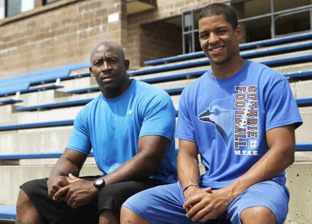 photo - Kai Callins, 17 of Guthrie (right), poses for a photo at Jelsma Stadium in Guthrie with his father Reggie Callins (left.) Kai Callins is recovering from a torn ACL last season, and his father has been his trainer throughout the recovery process. Photo by KT KING, The Oklahoman  KT King - KT KING