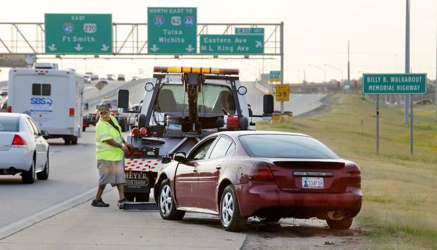photo - A wrecker operator tows a car that went into the Oklahoma River just west of Eastern Ave. in Oklahoma City Tuesday, July 15, 014. One person was in the car when it went into the river and was transported by ambulance. Photo by Paul B. Southerland, The Oklahoman