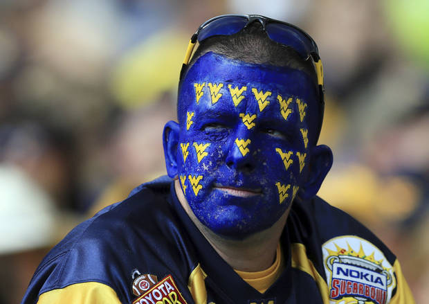 photo - A West Virginia football fan looks on in the crowd during a Sept. 22 game against Maryland in Morgantown, W.Va., With the Mountaineers joining the Big 12, WVU officials have asked fans to tone down their behavior and make Morgantown more hospitable for visitors. (AP Photo/Christopher Jackson)